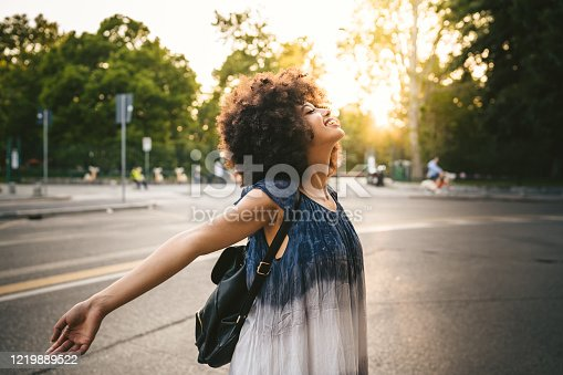 Young adult woman relaxing on the street at sunset in the city in summer opening your arms and looking upwards with closed eyes and smiling - Millennial is free and carefree