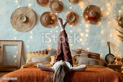 Dreamy and relaxed young adult woman lying on bed, raised legs up, resting in home at cozy bedroom in boho style
