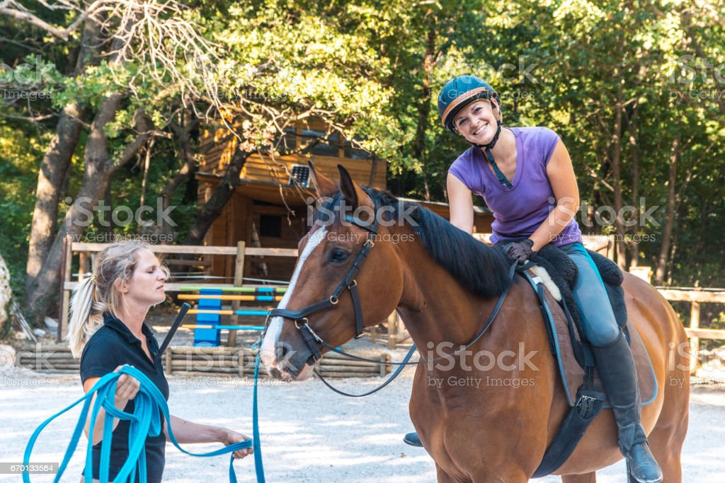Young Adult Woman Riding A Horse In Pasture stock photo
