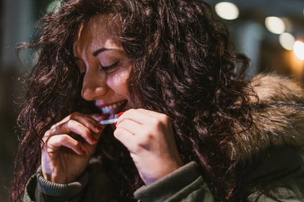 Young adult woman rolling a cigarette outdoor in the city at night stock photo