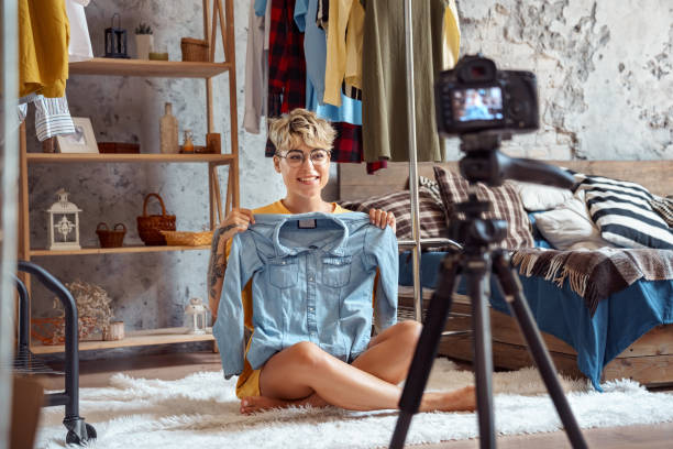 Young adult woman showing clothes and recording video on modern camera stock photo