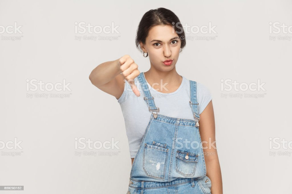 Young adult woman showing thumb down isolated on a gray background. . stock photo