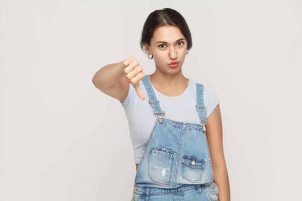 junge frau mit daumen nach unten isoliert auf einem grauen hintergrund. . - jeans overall stock-fotos und bilder
