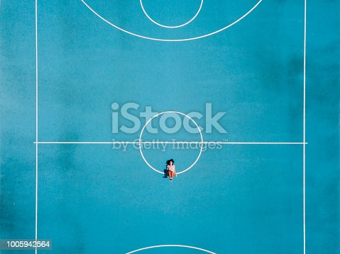 istock Young adult woman sitting on a surreal swing 1005942564