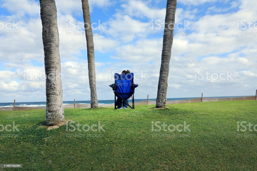 close up young adult woman sitting on outdoor chair on green...