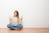 Young adult woman sitting on the floor over white brick wall at home showing and pointing up with fingers number ten while smiling confident and happy.