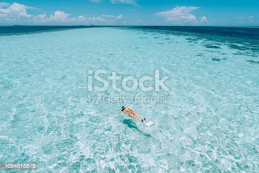 Young adult woman snorkeling in a turquoise clear sea