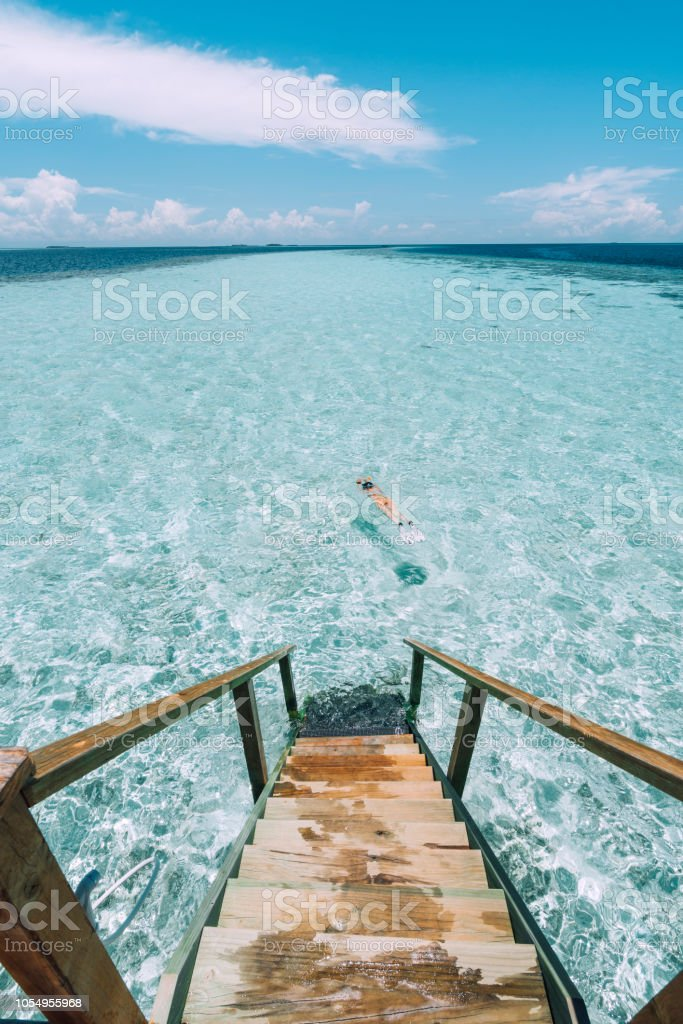 Young adult woman snorkeling in a turquoise clear sea stock photo