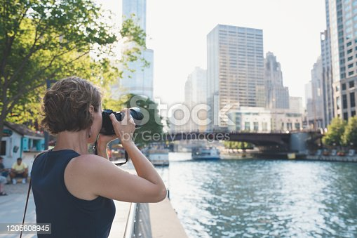 Young adult woman taking pictures in downtown Chicago