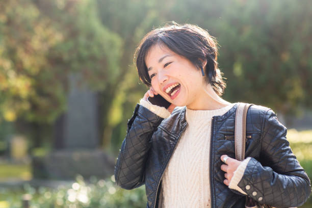 Young adult woman talking on the phone outdoors stock photo