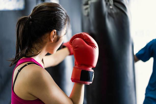 若い成人女性のボクシング ジムで半ば大人コーチとトレーニング - キックボクシング ストックフォトと画像