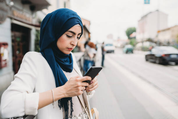 Young adult woman using a mobile phone while waiting for the bus in the city stock photo