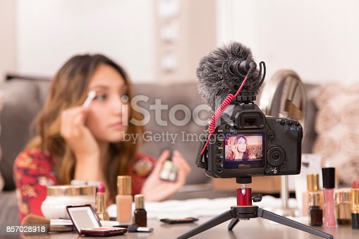 istock Young adult woman vlogging about cosmetics, skin care products. 857028918