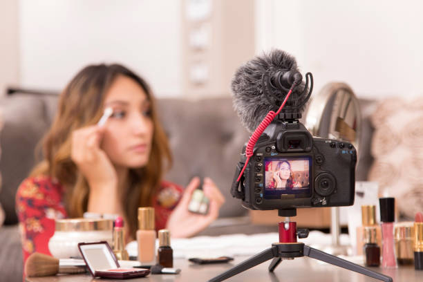 young adult woman vlogging about cosmetics, skin care products. - vlogger stock photos and pictures