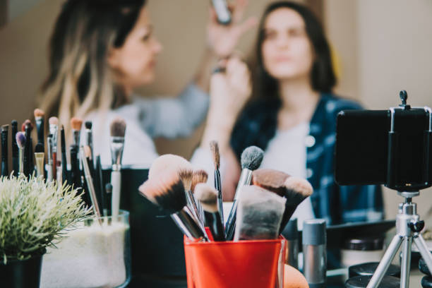 young adult woman vlogging about cosmetics, skin care products. - beautician stock photos and pictures