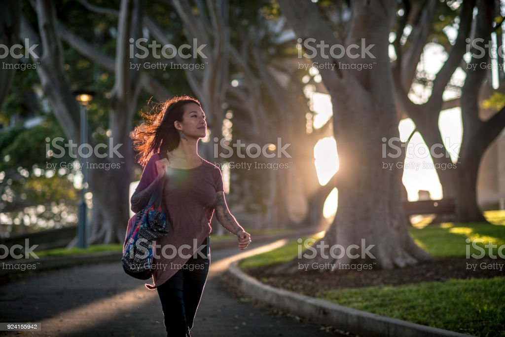 Young adult woman walking through the public park next to the Sydney Harbour Bridge stock photo