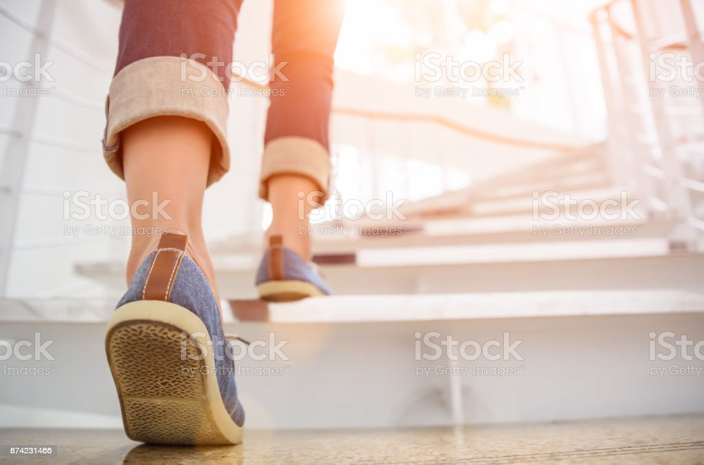 Young adult woman walking up the stairs with sun sport background. - fotografia de stock