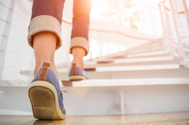 Young adult woman walking up the stairs with sun sport background. stock photo
