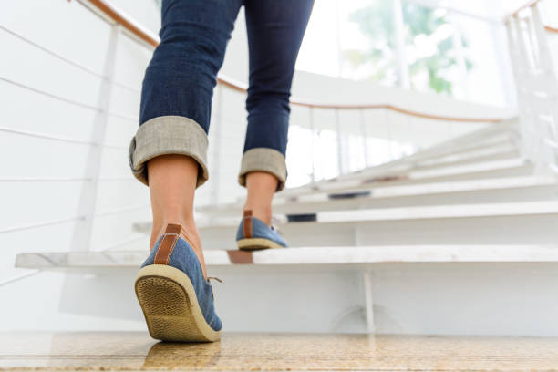young adult woman walking up the stairs with sun sport background. - staircase stock photos and pictures