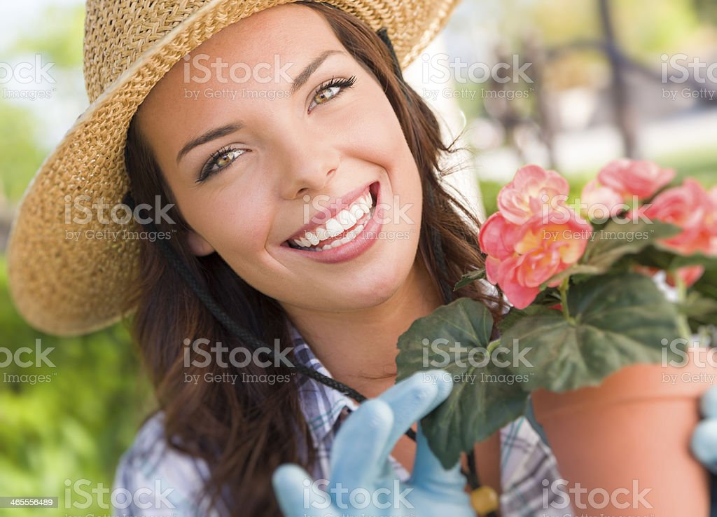 Young Adult Woman Wearing Hat Gardening Outdoors royalty-free stock photo