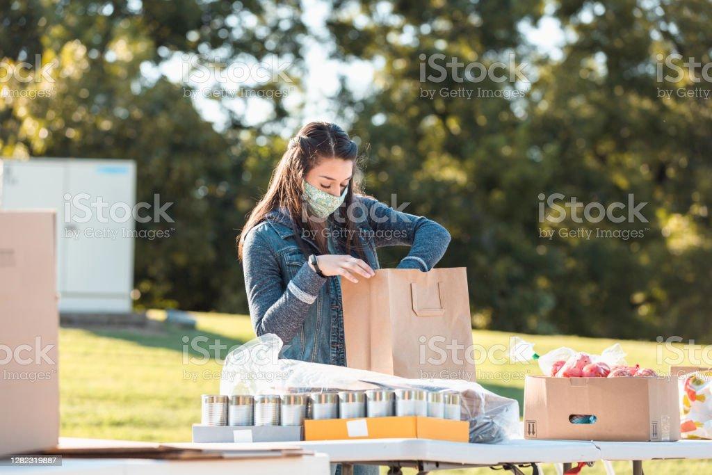 Joven mujer adulta usa máscara mientras clasifica los alimentos donados - Foto de stock de 20-24 años libre de derechos