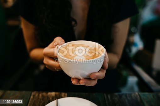 Young adult woman with a cappuccino at the coffee shop