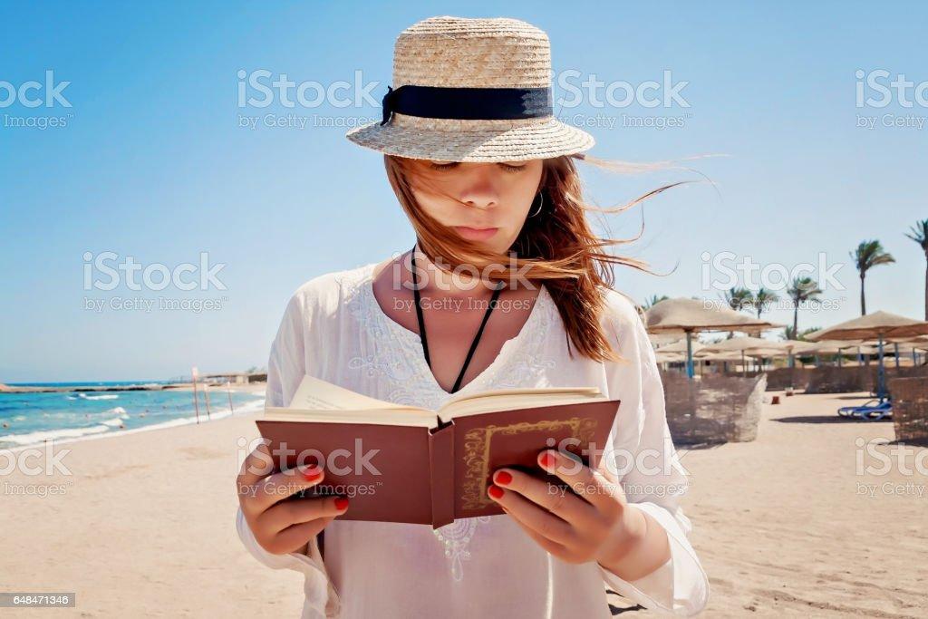 Jovem adulta, com um chapéu na praia, ler um livro - foto de acervo