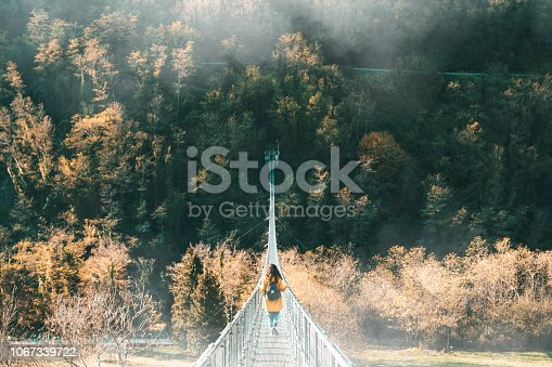 Young adult woman with a yellow jacket on a suspension bridge