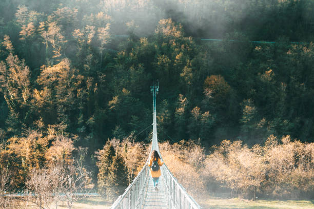 Young adult woman with a yellow jacket on a suspension bridge stock photo