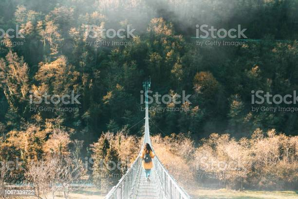 Photo of Young adult woman with a yellow jacket on a suspension bridge