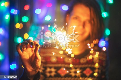 istock Young adult woman with bengal lights 1171563000