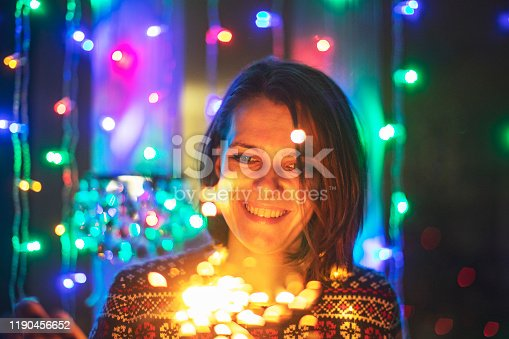 istock Young adult woman with bengal lights 1190456652