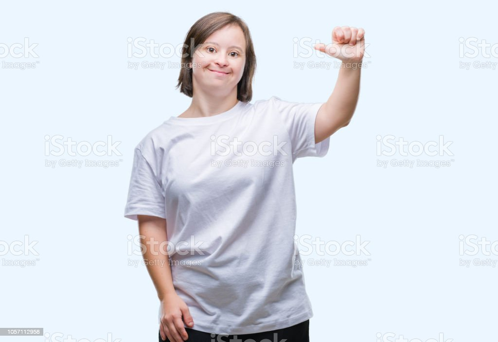Young adult woman with down syndrome over isolated background showing and pointing up with finger number one while smiling confident and happy. stock photo