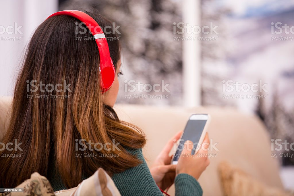 Young adult woman with headphones, smart phone at home. Winter. stock photo