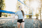 Friends practice playing volleyball at a beach court in Washington state, growing in their skill and ability as they practice serving and passing.  They pose for a portrait.