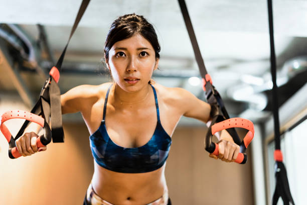 junge erwachsene frauen im am kreuz fitness-studio trainieren - konzentrationsübungen stock-fotos und bilder
