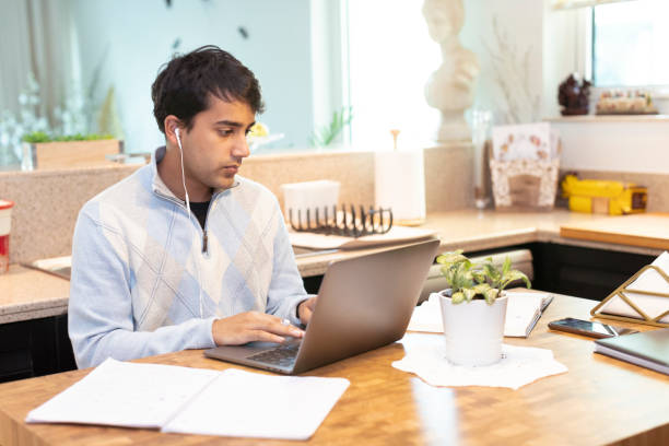 Young adult working from Home during COVID-19 Quarantine Lockdown stock photo