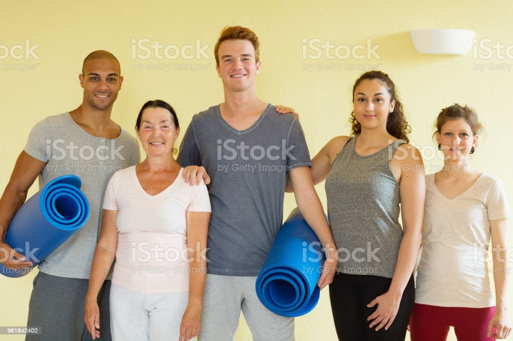 young adults after yoga class with mature teacher group portrait stock photo