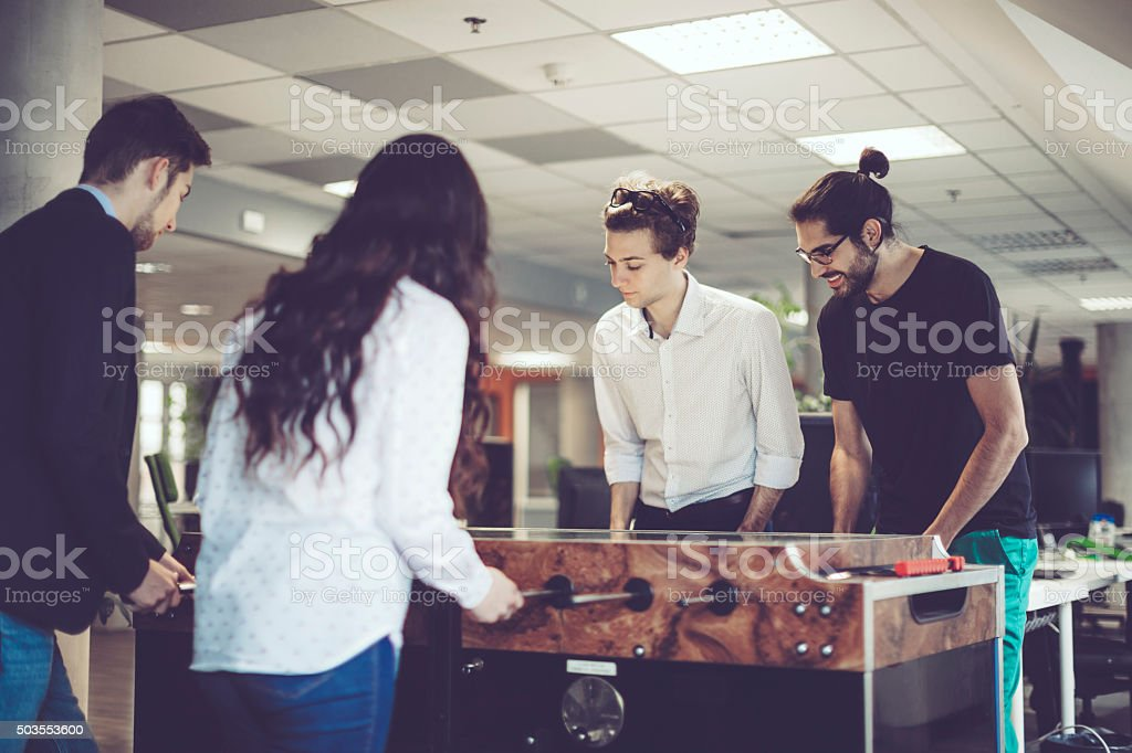 Young adults are playing foosball at work stock photo