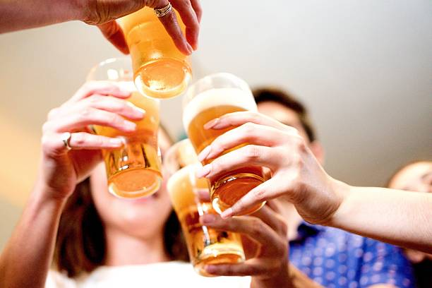 Young adults at a party toasting glasses of beer stock photo