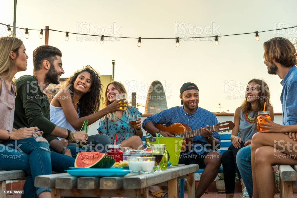 Young adults celebrating life and friendship on a rooftop in Barcelona, Spain. candid shot of eight young friends having fun on a rooftop party stock photo