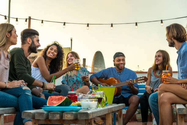 Young adults celebrating life and friendship on a rooftop in Barcelona, Spain. candid shot of eight young friends having fun on a rooftop party - foto stock