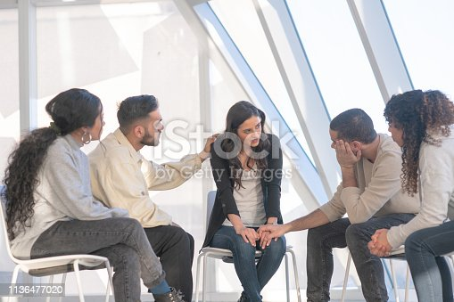 A group of diverse young adults sits in a circle of chairs one afternoon. They are having a group therapy session regarding their alcoholism. One friend consoles another with a gentle hand.