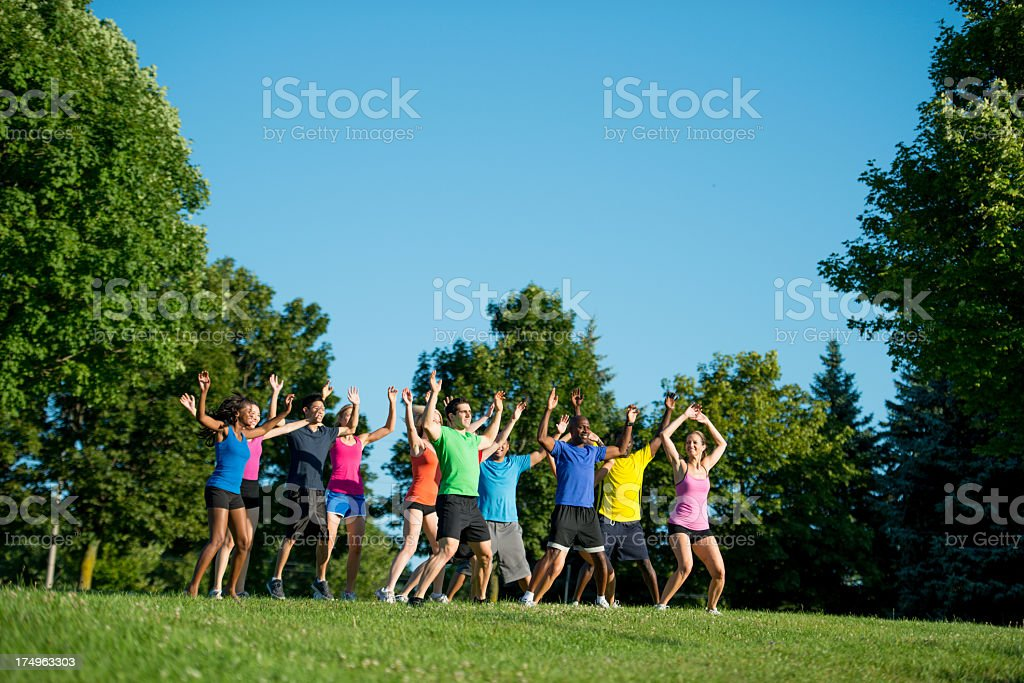 Young adults doing jumping jacks stock photo