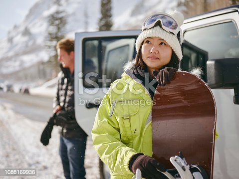 Young adults enjoying a winter outing, driving their vehicles in the mountains.