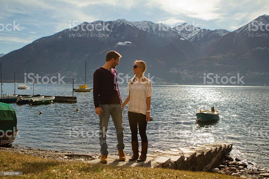 Young adults enjoying vacation near lake/mountain stock photo