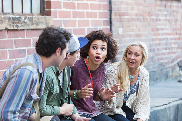 Young adults hanging out talking Four young multiracial adults, two men and two women, are hanging out together outside an old brick building.  An African American woman is talking, telling a story to her friends. storytelling stock pictures, royalty-free photos & images