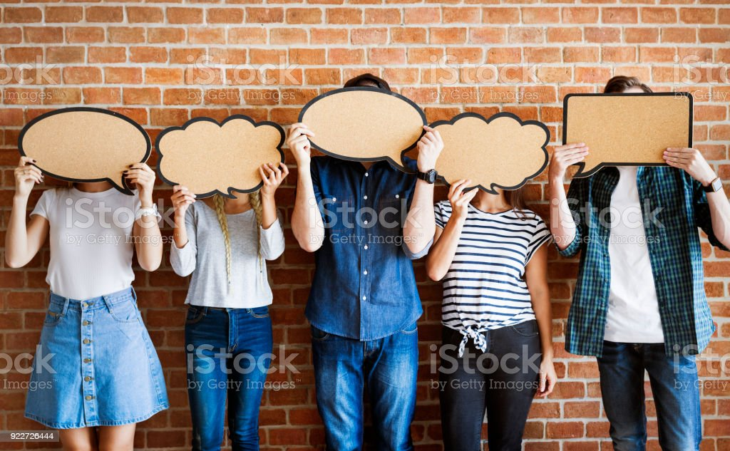 Young adults holding up copy-space placard thought bubbles stock photo