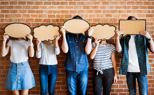 Young Adults Holding Up Copyspace Placard Thought Bubbles Stock Photo - Download Image Now