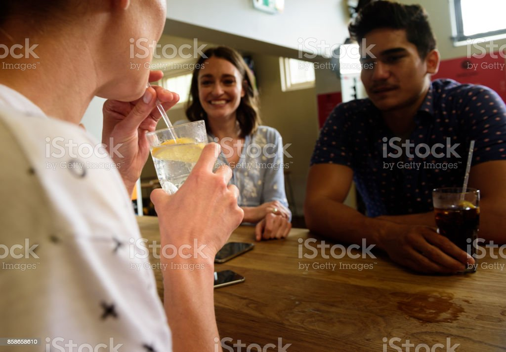 Young adults in bar, having fun, focus on drink stock photo